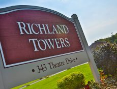 Richland Towers Address sign surrounded by greenery